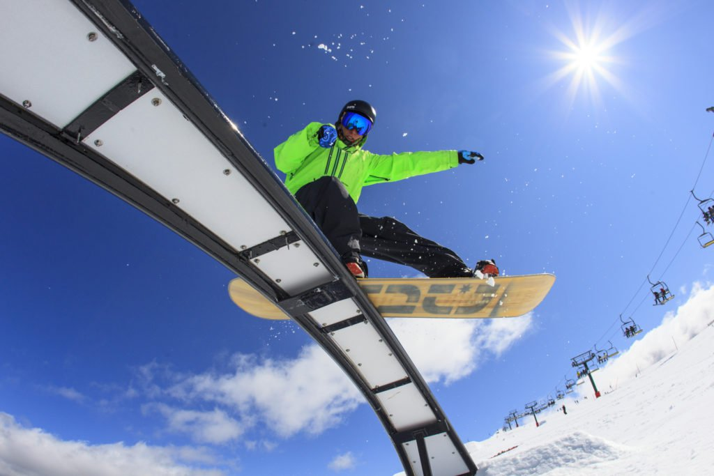 Snowboarder on rail at snow