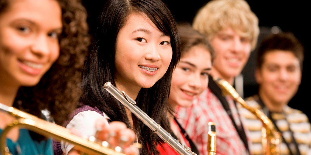 High-school girl playing flute with schoolmates