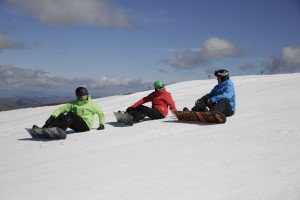 Snowboarders sitting on the slopes