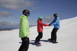 Snowboarders backwards on slopes cropped
