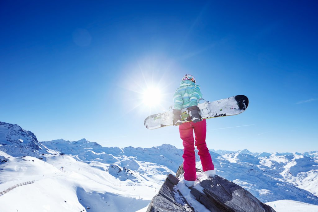 Back view of female snowboarder wearing colorful helmet, blue jacket, grey gloves and pink pants standing with snowboard in one hand and enjoying sunny alpine mountain landscape - winter sports concept