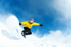 Man snowboarding mountain powder